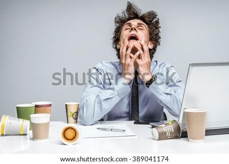 OMG! Frustrated man sitting desperate over paper work at desk. Negative emotion facial expression feeling - stock photo