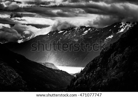 Ominous clouds over snow-capped mountains and a Pacific Ocean bay near Skagway, Alaska