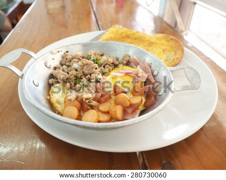 Omlette and slice bread on dish plate.