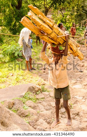 OMO, ETHIOPIA - SEPTEMBER 19, 2011: Unidentified Ethiopian boy carries wood. People in Ethiopia suffer of poverty due to the unstable situation - stock photo