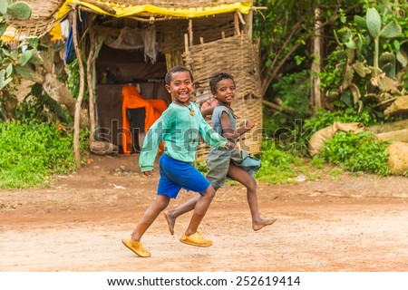 OMO, ETHIOPIA - SEPTEMBER 19, 2011: Unidentified Ethiopian boy runs screaming. People in Ethiopia suffer of poverty due to the unstable situation - stock photo
