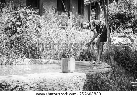 OMO, ETHIOPIA - SEPTEMBER 20, 2011: Unidentified Ethiopian man cleans his shoes. People in Ethiopia suffer of poverty due to the unstable situation