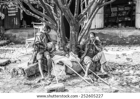 OMO, ETHIOPIA - SEPTEMBER 19, 2011: Unidentified Ethiopian men sit near a tree. People in Ethiopia suffer of poverty due to the unstable situation