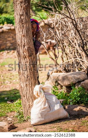 OMO, ETHIOPIA - SEPTEMBER 21, 2011: Unidentified Ethiopian woman behind a tree. People in Ethiopia suffer of poverty due to the unstable situation