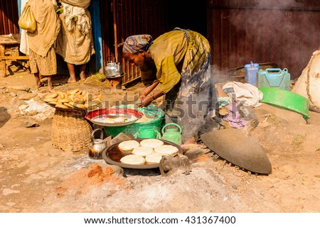 OMO, ETHIOPIA - SEPTEMBER 19, 2011: Unidentified Ethiopian woman makes pancakes at the local market. People in Ethiopia suffer of poverty due to the unstable situation - stock photo