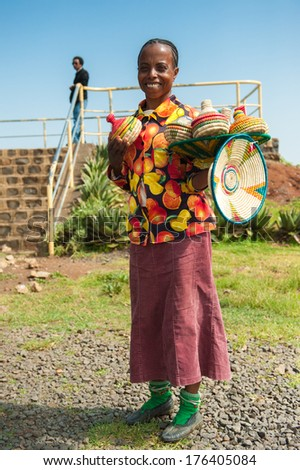 OMO, ETHIOPIA - SEPTEMBER 20, 2011: Unidentified Ethiopian woman sells traditional vases and wears tradtional clothes. People in Ethiopia suffer of poverty due to the unstable situation - stock photo