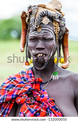 OMO VALLEY, ETHIOPIA - AUG 11: Mursi woman posing in the village,the ethnic groups in the The Omo valley Could disappear Because of Gibe III hydroelectric dam on Aug 11, 2011 in Omo Valley, Ethiopia. - stock photo