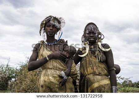 OMO VALLEY, ETHIOPIA - AUG 11: Mursi women posing in the village,the ethnic groups in the The Omo valley Could disappear Because of Gibe III hydroelectric dam on Aug 11, 2011 in Omo Valley, Ethiopia. - stock photo