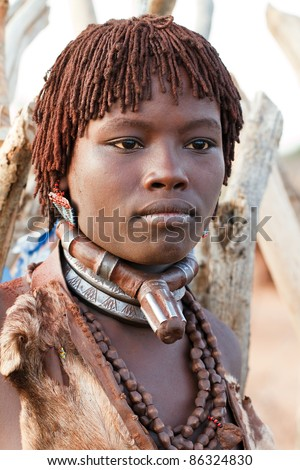 OMO VALLEY, ETHIOPIA - AUG 15: Unidentified Hamer woman in the village, the ethnic groups in the Omo valley could disappear because of Gibe III hydroelectric dam on Aug 15, 2011 in Omo Valley, Ethiopia. - stock photo