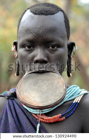 OMO VALLEY, ETHIOPIA - FEB 5: unidentified Surma woman posing in the village,the ethnic groups in the The Omo valley Could disappear Because of Gibe III hydroelectric dam on Feb 5, 2013 in Omo Valley, Ethiopia. - stock photo