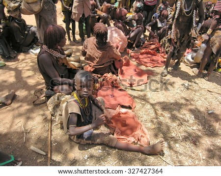 OMO VALLEY, ETHIOPIA - MARCH 13: Unidentified Hamer women sell ochre at market in Dimeka, March 13, 2012, Omo Valley, Ethiopia. Ochre is a natural earth pigment used by Hamer women to make hairdress. - stock photo