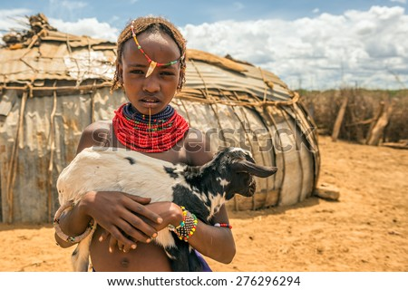 OMO VALLEY, ETHIOPIA - MAY 6, 2015 : Girl from the African tribe Dasanesh holding a goat in her village. - stock photo
