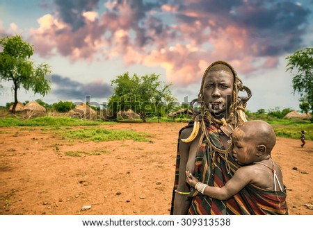 OMO VALLEY, ETHIOPIA - MAY 7, 2015 : Woman from the african tribe Mursi with her baby and traditional horns in Mago National Park, Ethiopia - stock photo