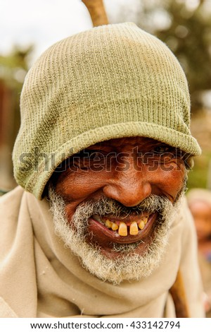 OMO VALLEY, ETHIOPIA - SEP 22, 2011: Unidentified Ethiopian funny man with beard and green hat in Ethiopia, Sep.22, 2011. People in Ethiopia suffer of poverty due to the unstable situation - stock photo