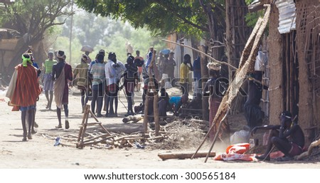 OMORATO, LOWER OMO VALLEY, ETHIOPIA - JANUARY 31, 2012: Unidentified people on the street in traditional village of Dassanech tribe.  Omorato one of the poorest places in Ethiopia. - stock photo