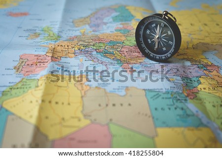 ompass on the tourist map. Focus on the compass needle. - stock photo