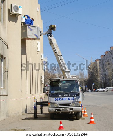 OMSK, RUSSIA - APRIL 22, 2010: Team of technical service workers mounts air conditioner on outside wall of house - stock photo