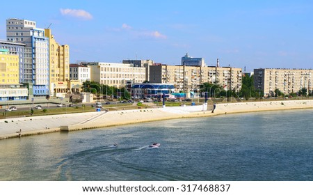 OMSK, RUSSIA  - AUGUST 05, 2010: Views Irtysh river with sailing speedboat, embankment with buildings and walking people