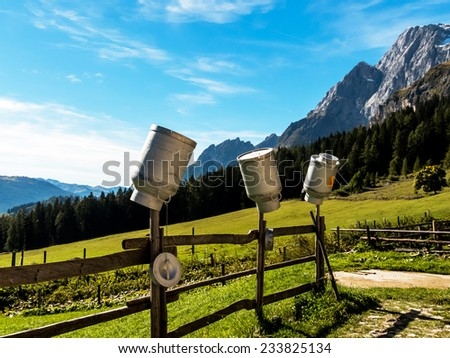 on a beautiful pasture milk jugs hanging on to dry. - stock photo