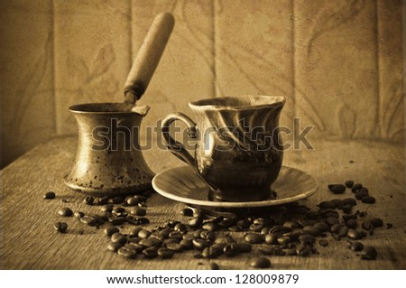 on a brown table scattered grains of black coffee and a cup of hot coffee