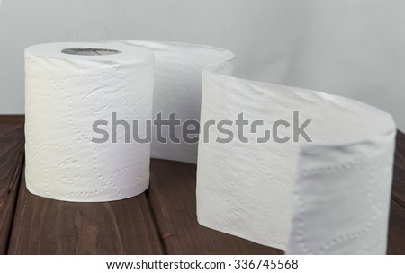 On a brown wooden background white soft roll unwound in the way of toilet paper  - stock photo