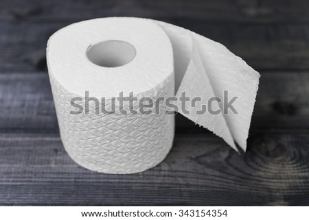 On a brown wooden background white soft roll unwound in the way of toilet paper