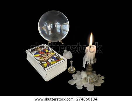 On a dark background in the light of the candles the tools of the magician: crystal ball, Tarot cards, crystal ball and a bottle of magical liquid. - stock photo