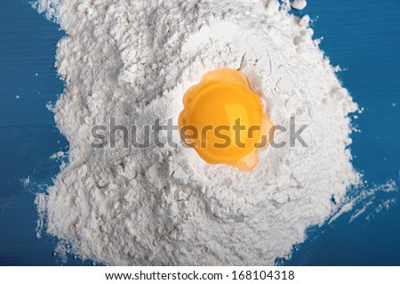 on a dark blue cook-table the small group of flour is poured where outpoured yolk of raw egg