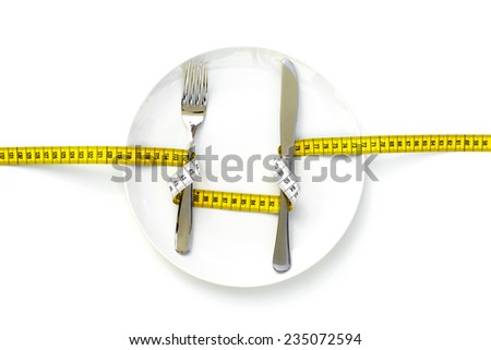 ON A DIET A fork and a knife wrapped with a measure and placed on an empty dish.