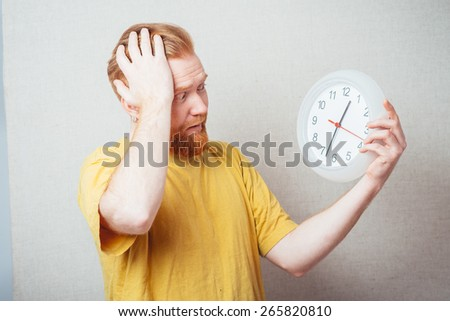 on a gray background man with a beard in a yellow shirt holding a clock and scared