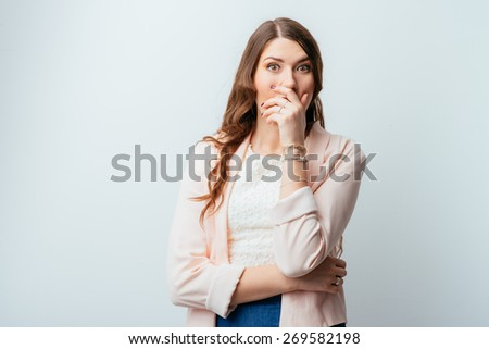 on a gray background young girl covers her mouth in shock hand - stock photo