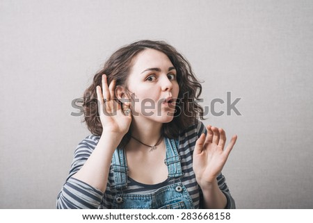 on a gray background young girl overhears - stock photo