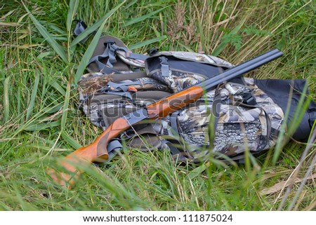 on a halt, hunting gun and backpack - stock photo