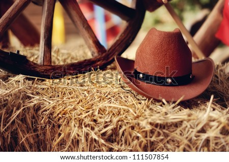 on a haystack the brown cowboy's hat and a wooden wheel lies - stock photo