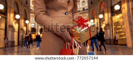 On a huge Christmas sales in Italian fashion capital. Closeup on Christmas gift and shopping bags in hands of woman with Christmas gift and shopping bags in Galleria Vittorio Emanuele II in Milan