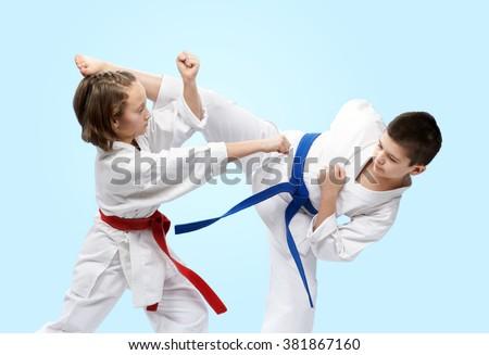 On a light background athletes train blocks and kicks of karate - stock photo