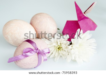 On a light background three Easter eggs, flowers and a rabbit origami - stock photo