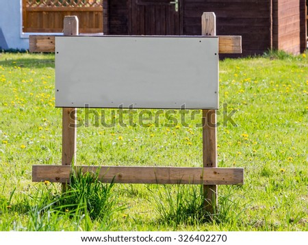 """on a meadow there is a sign """"land for house for sale"""". site for a new home. - stock photo"""