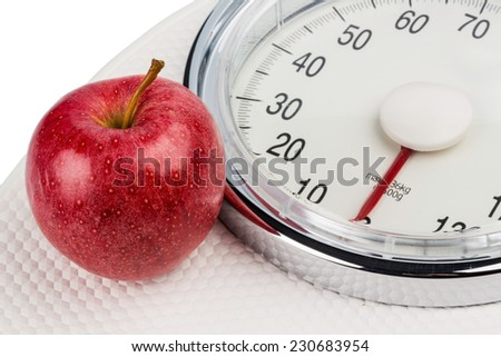 on a personal scale is an apple. photo icon for slimming and healthy, vitamin-rich diet. - stock photo