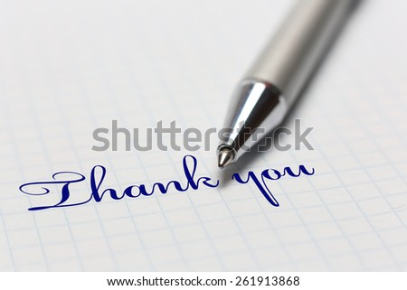 "On a piece of the cell shows ""thank you"" and a pen - stock photo"