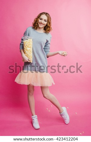 on a pink background girl in a dress holding a popcorn bag - stock photo