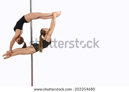 On a pole. Two young sporty girls in dangerous acrobatic position on a pole - stock photo