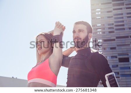 On a sunny day, a beautiful young couple in sportswear does stretching outdoors. - stock photo