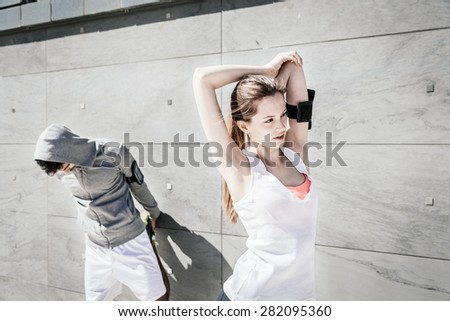On a sunny day, a beautiful young couple in sportswear does stretching outdoors - stock photo