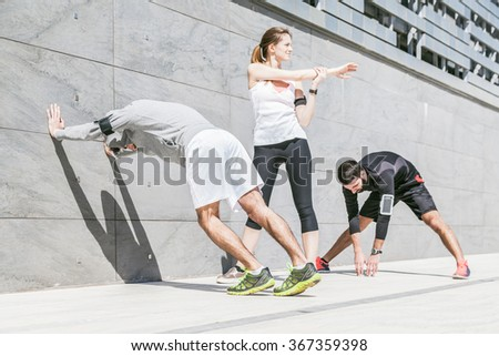 On a sunny day, three friends in sportswear does stretching outdoors near a building - stock photo