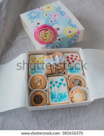 on a table decorated with a beautiful box with cookies and flower