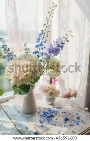 on a table in the sun and gentle pink hydrangea flower petals - stock photo