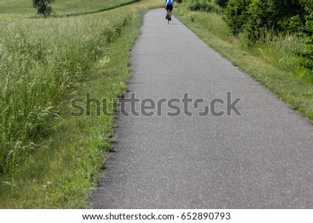on a very sunny day in june in south germany you see bicyclist driving and jogger running along a trail