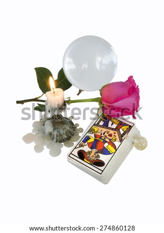 On a white background burning candle and the tools of the magician: Tarot cards, a bottle of magic liquid, a crystal ball and a symbol of love - scarlet rose. - stock photo