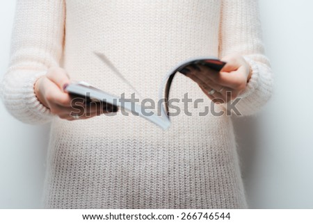 on a white background girl leafing through a magazine - stock photo